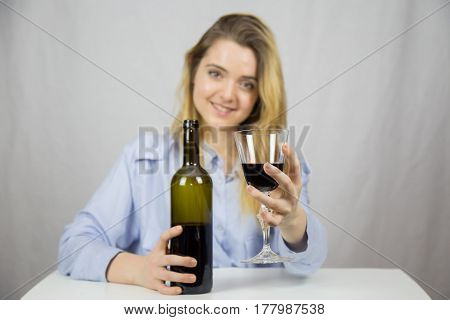 Young Caucasian white woman sitting at a table while drinking wine. She is blonde and pretty with light brown eyes. The background of the image is white.