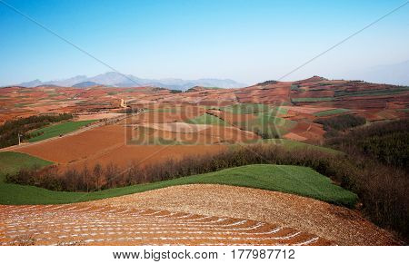 Brown sand agriculture landscape at midday with mountains and green hills at the background and nobody around China.