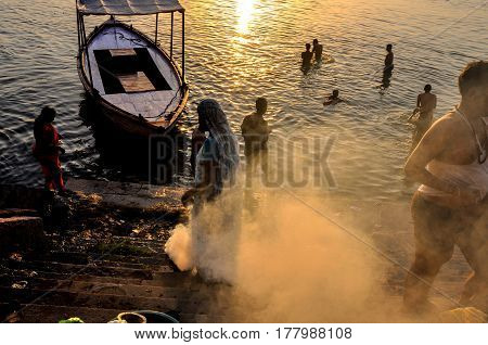 Varanasi Uttar Pradesh India- October 3 2013: Devotees taking bath and a women burning waste material at the bank of Holy River Ganges in Varanasi Uttar Pradesh India. Varanasi is the second oldest city in the world situated at the bank of river Ganges.