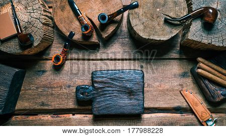 Tobacco and pipes on wood stands and boards. Brown shades. Tools for slicing twist tobacco. Close-up top view