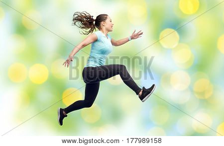 sport, fitness, motion and people concept - happy smiling young woman jumping in air over summer green lights background
