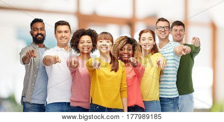 diversity, choice, ethnicity and people concept - international group of happy smiling men and women pointing finger on you over office background