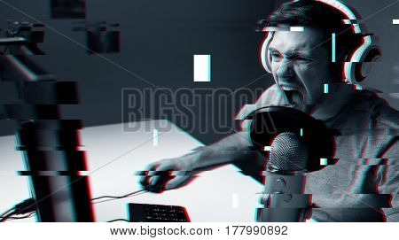 technology, gaming, entertainment and people concept - angry screaming young man in headset with pc computer playing game at home and streaming playthrough or walkthrough video over glitch effect