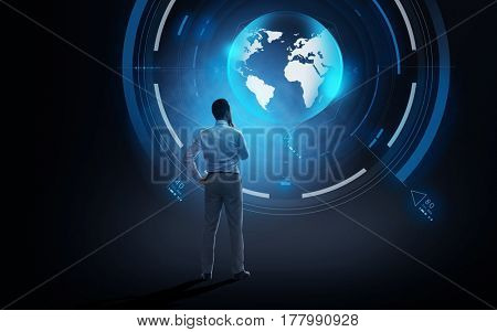 business, people, technology and mass media concept - businessman looking at virtual earth projection over dark background from back