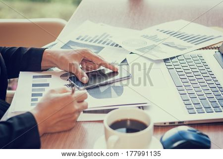 Close Up businessmen working at a coffee shop with a document with a smartphone and a laptop computer.