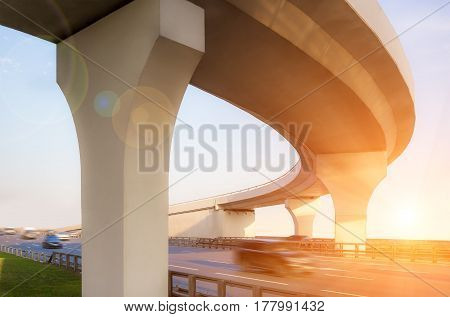 View from below to a concrete overpass with lensflare effect