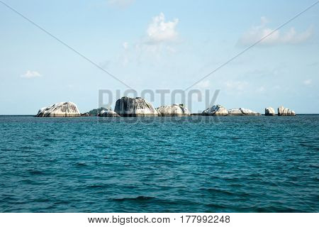 Natural rock formation in sea at Belitung Island in the afternoon and white lighthouse at the background Indonesia.