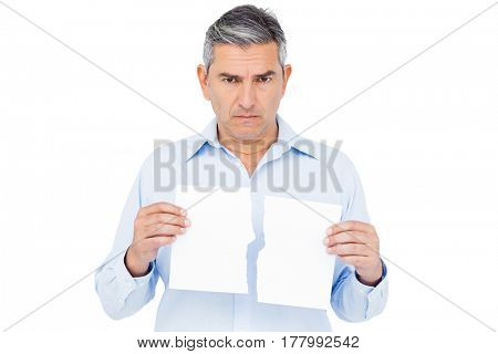 Stern man holding ripped paper on white background
