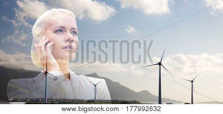 business, sustainable energy, technology and people concept - serious businesswoman with smartphone talking over wind turbines