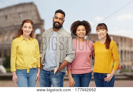 diversity, travel, tourism and people concept - international group of happy smiling men and women over coliseum background