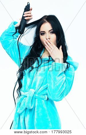 pretty cute yawning sleepy sexy girl or beautiful woman with fashion makeup do hairstyle and posing in turquoise velour bathrobe with straightener isolated on white background