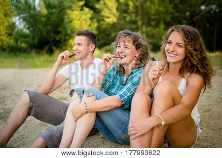 Mother with her two children enjoying sweet chocolate bar