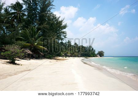Tropical stretched out white sand beach and palm trees with blue colored ocean seashore water in the afternoon at Tanjung Pinang on Bintan island Indonesia.
