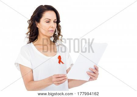 Woman wearing red aids awareness ribbon reading test result on white background