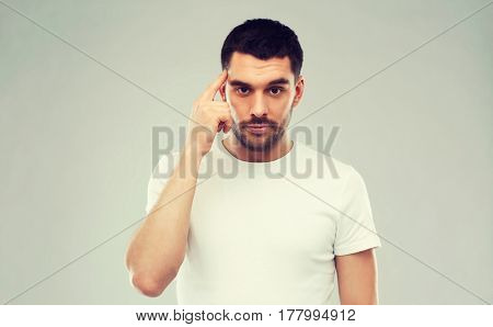 advertisement, idea, inspiration and people concept - man pointing finger to his temple over gray background