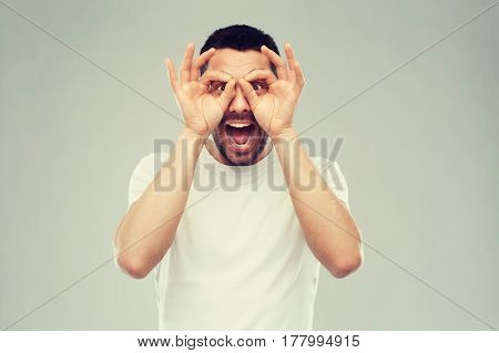 fun and people concept - man making finger glasses over gray background