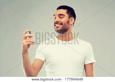 perfumery, beauty and people concept - happy smiling young man with male perfume over gray background