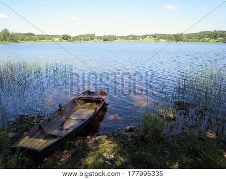 An old boat at edge of lake.