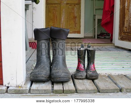 Two pairs of boots left on the porch.