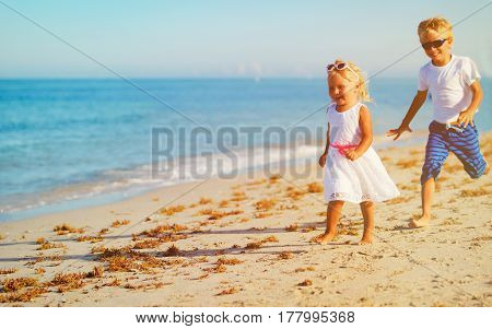 happy little boy and girl running at beach