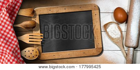 Baking background with empty blackboard on a wooden table with flour egg rolling pin kitchen utensils and red and white checkered tablecloth