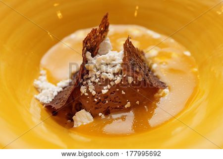 Chocolate ice cream and fruit pulp dessert in yellow plate, close-up