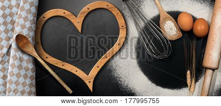 Baking background with empty blackboard in the shape of a heart on a black table with rolling pin whisk eggs spoons ears of wheat and a checkered tablecloth