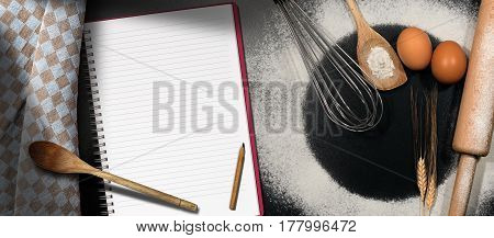 Baking background with empty notebook for recipes or ingredients list on a black table with flour eggs whisk rolling pin spoons and a checkered tablecloth