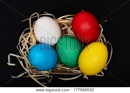 Easter Colorful Eggs In Basket With Straw Nest On Black