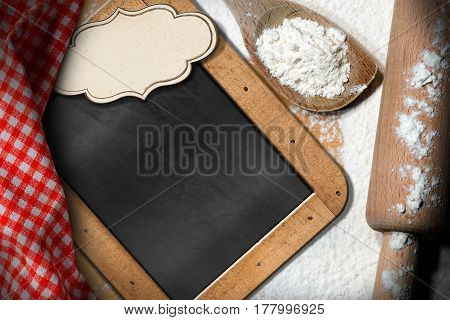 Empty blackboard and label with copy space on a table with white flour wooden rolling pin spoon and red and white checkered tablecloth