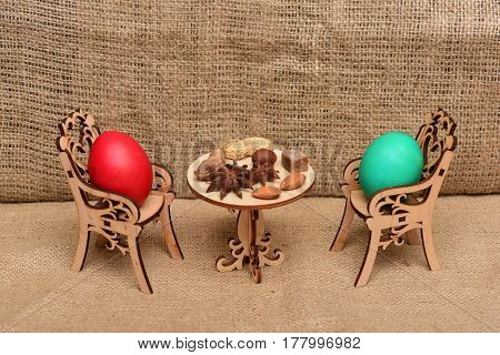 painted easter egg in wooden chairs at table with badian or star anise spice and nuts in dining room on wood background spring holiday celebration
