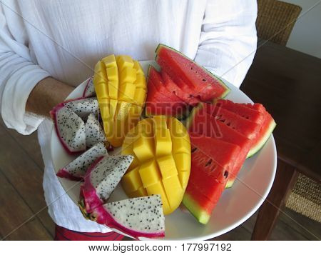 A plate of fresh fruit - mangoes, watermelon and dragon fruit.