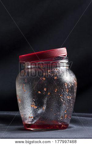Empty fruity jam jar on table on dark background