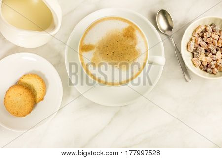 A cup of latte with butter cookies, a milk jar, and cane sugar on a white marble table, with a place for text. Selective focus
