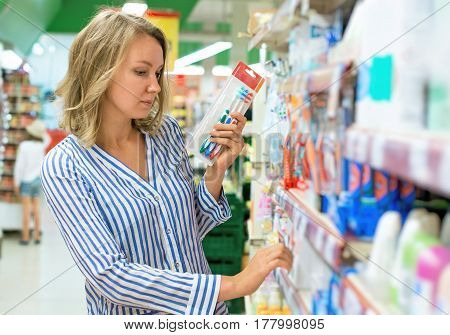 Young Woman Is Choosing Toothbrush In Supermarket.