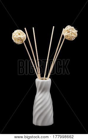 Decorative ceramic vase with wooden chopsticks on a black background