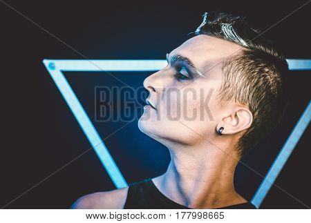 Portrait of beautiful young man with modern hairstyle, artistic multicolor makeup. Studio shot. Black background
