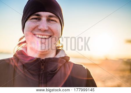 Man in sports clothes smiling outdoors. close-up
