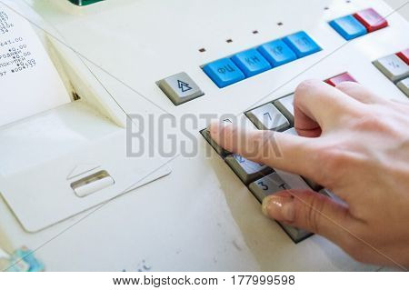 Close-up image of a shop-assistant's hand pressing a key of an electronic cash machine in a shop.