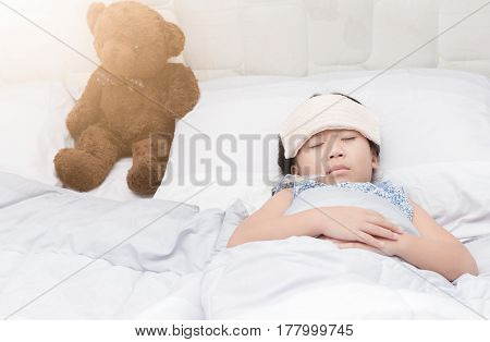 Sick girl with thermometer laying in bed child fever and illness