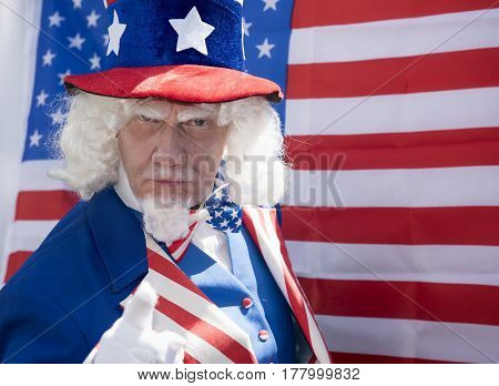 Portrait image of a man dressed a Uncle Sam. Standing in front of an American Flag.