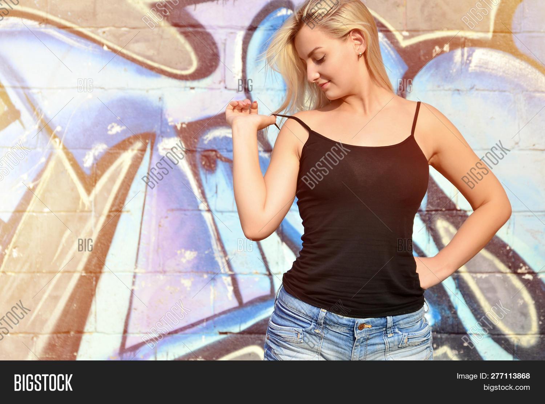 4312077fa3 Sexy Caucasian Blonde Girl In Denim Shorts And Black Tank Top Posing  Against Graffiti Wall In