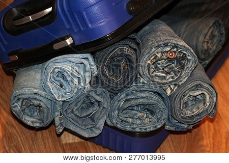 A Stack Of Blue Jeans In A Blue Suitcase, Fashion