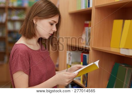 Sideways Shot Of Serious College Female Student Focused In Book, Poses In School Library, Chooses Ne