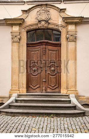 Old Door Of A Historical Building With Coats Of Arms Made Of Stone