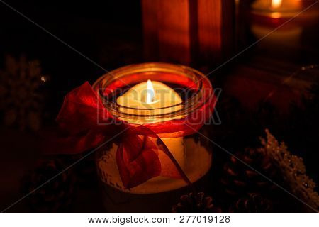 Burning Candle In A Glass And Fir Cones In The Dark