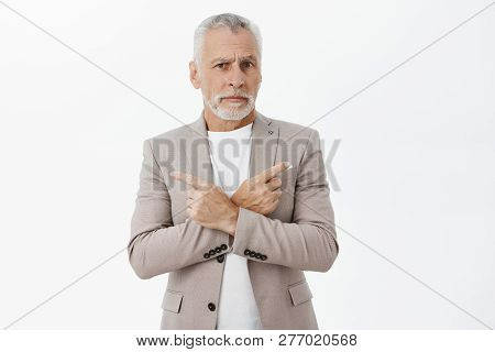 Unsure And Questioned Handsome Old Businessman With White Hair And Beard Standing In Elegant Formal