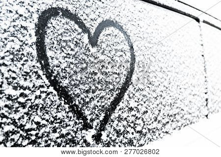 Heart Symbol On Frozen Window Of The Car. Shape Of Heart Drawn On Snow On Front Window Of The Car. H