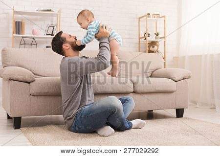 Friendship Of Father And Son. Man And Little Boy Looking At Each Other, Baby Grabs Daddys Beard, Sit