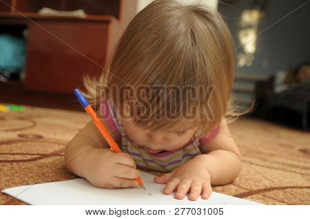 Baby Girl Learning To Write And Paint In Home Environment Lying On Carpet. Early Brain Education Dev
